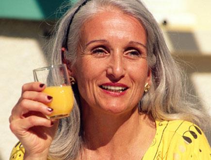 אישה מבוגרת עם שיער אפור שותה מיץ לבושה צהוב (צילום: jupiter images ,jupiter images)
