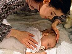 אמא מלטפת את התינוקת שלה שישנה בלול