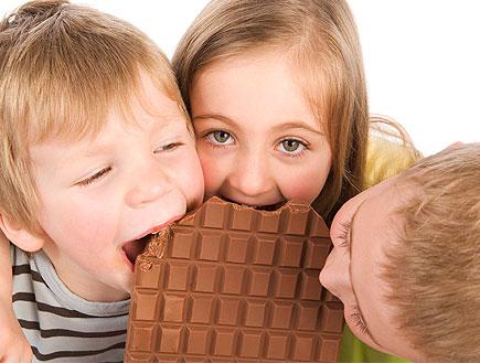 שלושה ילדים נוגסים בחפיסת שוקולד (צילום: jupiter images ,jupiter images)