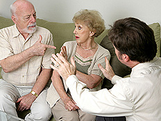 זוג מבוגר יושב על ספה מתווכח ובחור צעיר מנסה לגשר