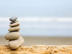הרבה אבנים מונחות אחת על השניה מול הים