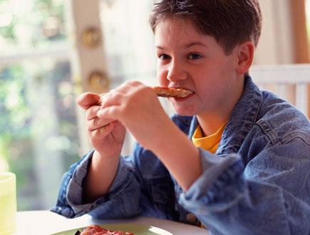 ילד בז'קט ג'ינס אוכל משולשי פיצה (צילום: jupiter images ,jupiter images)