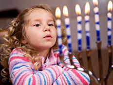 ילדה עם פסים מסתכלת על נרות דלוקים בחנוכיה