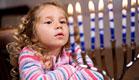 ילדה עם פסים מסתכלת על נרות דלוקים בחנוכיה (צילום: istockphoto ,istockphoto)