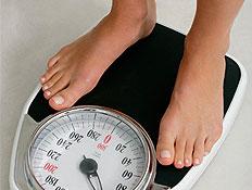 כפות רגליים עומדות על משקל שחור ברקע לבן