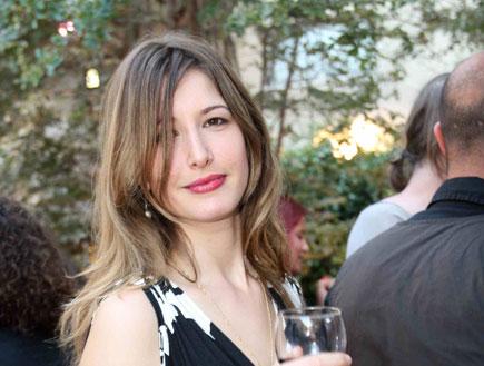 שירה קצנלנבוגן בשימלה שחור לבן עם כוס יין ביד
