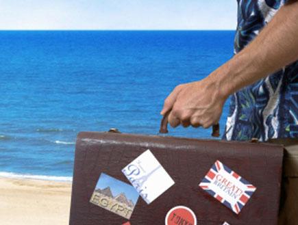 איש בחולצה פרחונית מחזיק מזוודה (צילום: istockphoto)