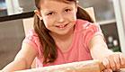 ילדה בורוד לשה בצק עם מערוך ומחייכת (צילום: jupiter images ,jupiter images)