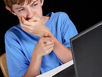 ילד בכחול יושב מול מחשב ומכסה את פיו(istockphoto)