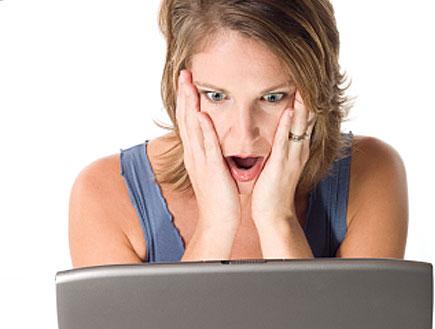 אישה מביטה בלפ טופ ומחזיקה את פניה בדאגה