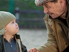 זקן וילד בכובע מחזיקים ידיים ברחוב ומסתכלים זה על זה