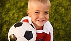 ילד בלונדיני באדום על דשא מחזיק כדורגל ומחייך (צילום: jupiter images ,jupiter images)