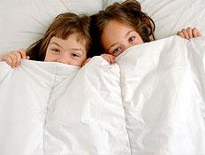 שתי ילדות מציצות משמיכת פוך לבנה במיטה