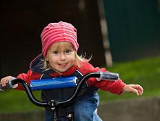 ילדה בכובע ורוד על אופניים מוציאה לשון