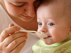 אישה מאכילה בכפית תינוק מחייך לבוש ירוק
