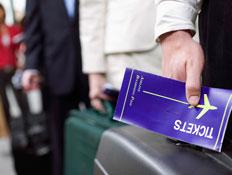 יד אוחזת מזוודה וכרטיס טיסה
