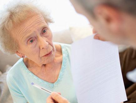 איש מחזיק נייר ועט מול אישה מבוגרת בתכלת