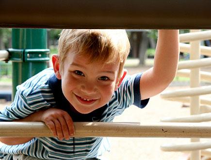 יום כיף: ילד מציץ מבעד לברזלים של מתקנים בגן שעשוע (צילום: istockphoto ,istockphoto)