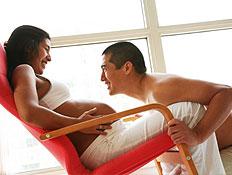 גבר נשען על אישה בהריון באדום שיושבת בכיסא מחייכים