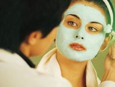 עור נשים- אישה מורחת מסכה על פנים של בחורה