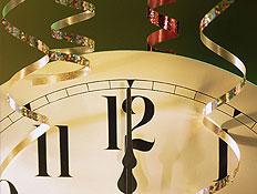 קלוז אפ של שעון קיר בשעה 12:00 על רקע ירוק