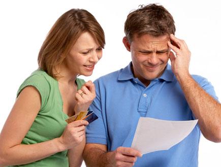 איש בכחול תופס ראש ונייר ביד אישתו מבוהלת עם אשראי (צילום: jupiter images ,jupiter images)