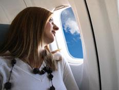 אישה במטוס, יושבת בכסא ליד החלון