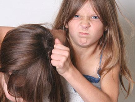 ילדה בפרצוף כועס מושכת בשיער לילדה אחרת (צילום: istockphoto ,istockphoto)