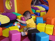 פעוט בצהוב משחק עם כדור ומסביבו קוביות במתקן ג'ימב