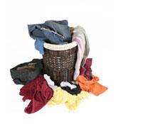 סל כביסה חום מקש מלא בגדים זרוקים מסביב