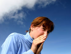 אישה ג'ינג'ית מקנחת את האף