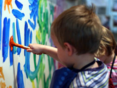שני ילדים בפסים מציירים במכחול על קיר