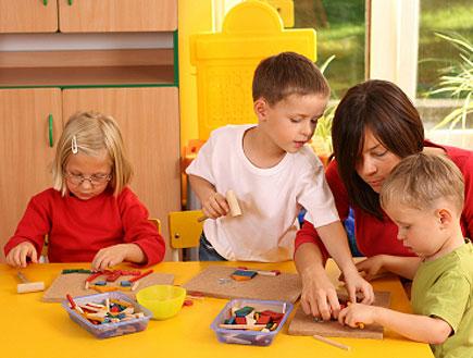 אישה באדום משחקת עם שלושה ילדים בגן שקוף (צילום: istockphoto ,istockphoto)