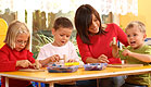 אישה באדום משחקת וצוחקת עם שלושה ילדים בגן שקוף (צילום: istockphoto ,istockphoto)