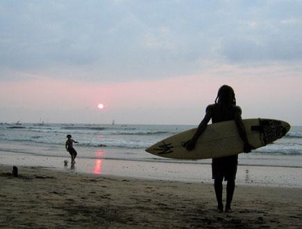 גולש מחזיק גלשן בחוף תמרינדו בקוסטה ריקה