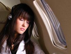 בחורה ישנה עם אוזניות במטוס ונהנית מהטיסה
