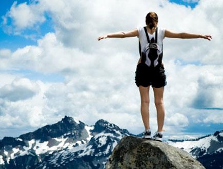 חופש - אישה עומדת על פסגת הר ופורשת ידיים לצדדים(iStock)