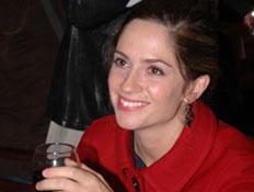 טלי שרון במעיל אדום עם כוס יין ביד מחייכת