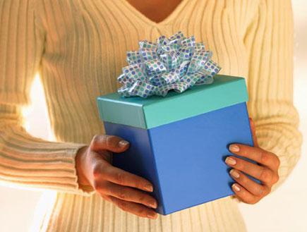 גוף אישה בסריג לבן מחזיקה קופסת מתנה כחולה עטופה ב(jupiter images)