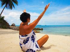 אישה יושבת בחוף ים, מרימה ידיים לאוויר
