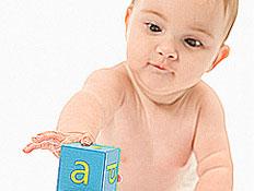 תינוק ערום מושיט יד למגדל קוביות של אותיות באנגלית