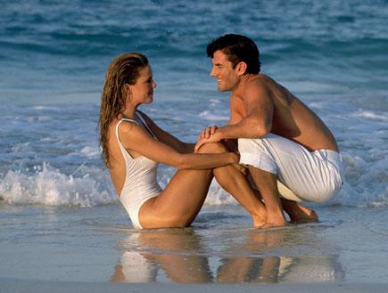גבר ואישה בבגד ים יושבים על שפת הים