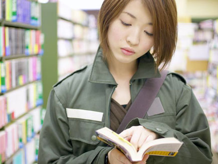 יפנית מעיינת בספר בספריה(jupiter images)