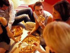 אוכל ומזלות-חברים יושבים ואוכלים פיצה