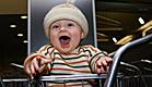 תינוק עם פסים צוחק בעגלה בצ'ק אין (צילום: dbabbage, Istock)