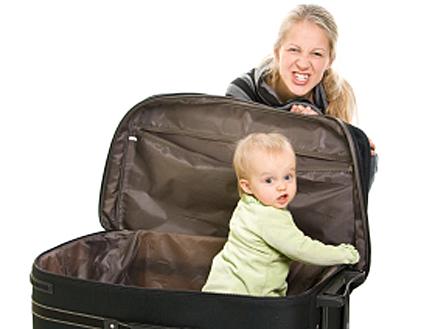 תינוק במזוודה פתוחה ומאחוריה בחורה עושה פרצוף (צילום: istockphoto ,istockphoto)