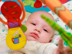 תינוק שוכב ומשחק עם מוביילים צבעוניים (צילום: istockphoto ,istock)