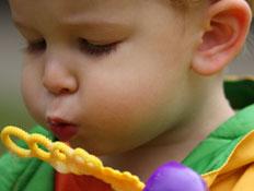 פעוט נושף על צעצוע של בועות סבון (צילום: istockphoto ,istock)