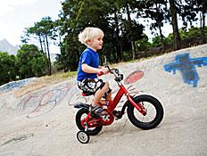 ילד בלונדיני רוכב על אופניים אדומות
