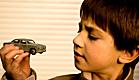 ילד בחולצה חומה מסתכל אל מכונית צעצוע (צילום: RMAX, Istock)